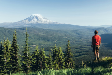 Male hiker on a mountain summit, looking at the landscape towards Mount Hood