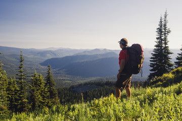 Man backpacking in the mountains, walking on a ridge overlooking a valley.