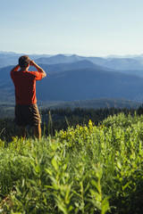 A man standing on a mountain ridge, taking a photograph of the landscape and forested valley.
