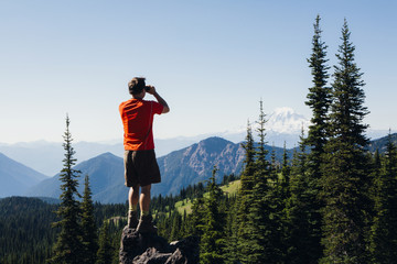 A man standing on a mountain ridge, taking a photograph of the landscape.