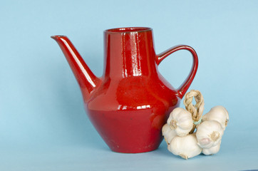 red ceramic jar pitcher and healthy garlic bunch
