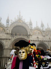 Piazza San Marco and the Basilica San Marco. A stall selling carnival masks and hats.