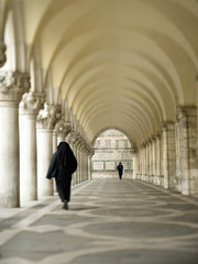 Piazza San Marco is a large square surrounded by arcades and a series of columns. Two people walking.
