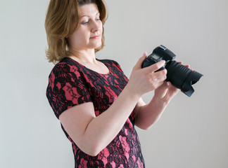 Woman with a camera on  light background