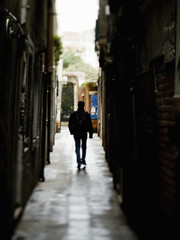 A man walking down a narrow alleyway in shadow.