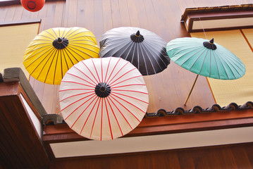 Colorful Japanese umbrella with wooden house background