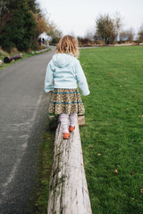 View from behind of a four year old girl walking and balancing on a log.