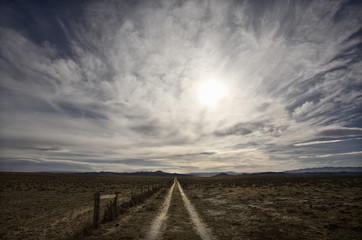 A big sky with clouds over the prairie, and a dirt road track leading into the distance.