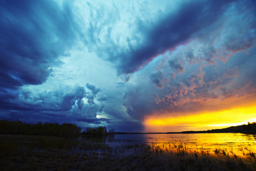 Sunset on the horizon over a lake, and storm clouds rising.