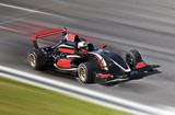 Fototapety F1 race car racing on a track with motion blur