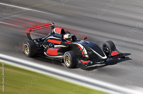 F1 race car racing on a track with motion blur - 80445795