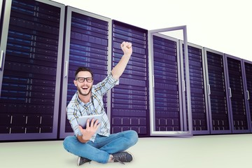 Composite image of handsome hipster using tablet pc and cheering