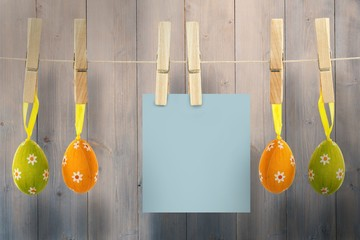 Composite image of hanging easter eggs and card