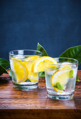 Glasses with drink, slices lemon and mint.