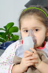 Little girl using an inhaler indoors.