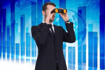 Elegant businessman standing and using binoculars