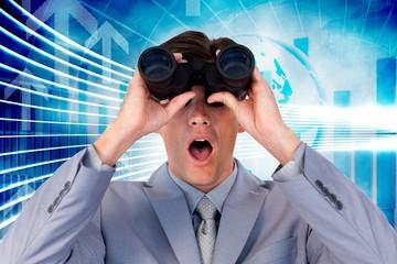 Suprised businessman looking through binoculars