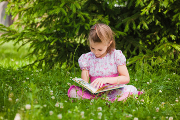 girl is  reading on the grass