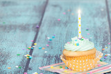 Pastel cupcake with a candle on vintage background