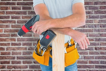 Male carpenter with power drill and plank