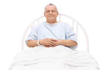 Cheerful mature patient lying in a hospital bed