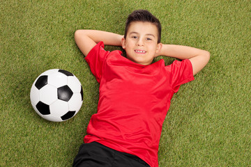 Carefree boy in a red football jersey lying on grass