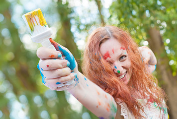 Laughing woman with the paitbrush is ready for creative battle