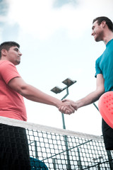 friends shaking hands in paddle tennis