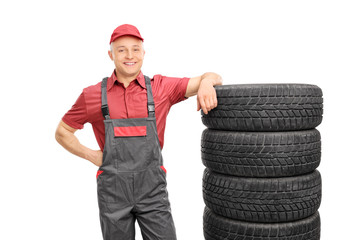 Male mechanic leaning on a stack of tires
