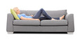 Young blond woman sleeping on a gray sofa