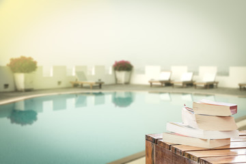 books on table at swimming pool