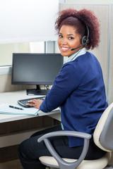 Happy Female Customer Service Executive Using Computer