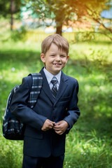 male elementary school student with backpack on green background