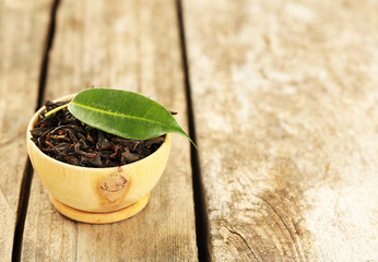 Black tea with leaf in bowl on old wooden table