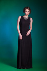 Portrait of beautiful young woman in evening black dress