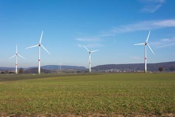 Windrad auf Bergkuppe mit Feld und blauem Himmel
