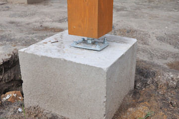 Closeup of wooden pillar on the construction site with screw