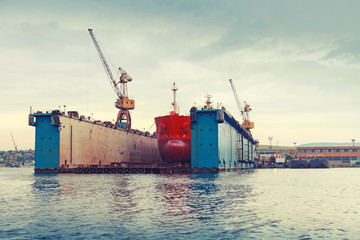 Floating dry dock with red tanker under repair