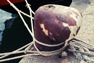 Old rusted mooring bollard with naval ropes
