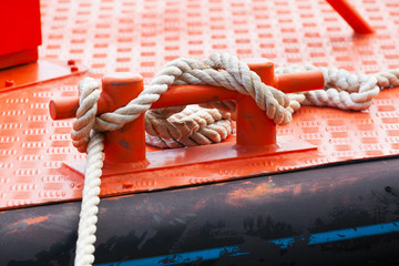 Red steel bollard with ropes mounted on deck