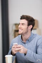 attraktiver mann mit handy im büro