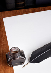 Quill, inkwell and a blank piece of paper.