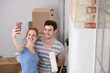 glückliches paar macht ein selfie beim umzug in neue wohnung - 80458937