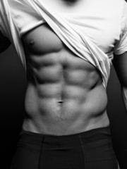 B/w closeup photo of an athletic guy with perfect abs