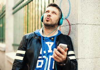Young man with headphones playing with smart phone