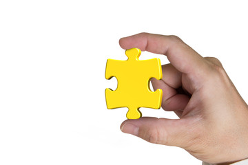 Hand holding gold jigsaw puzzle piece isolated on white