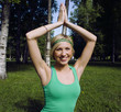 blonde real girl doing yoga in green park on grass
