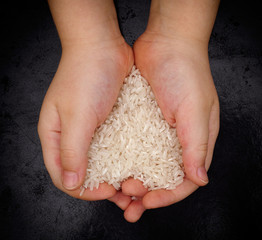 Child holds white rice in his hands