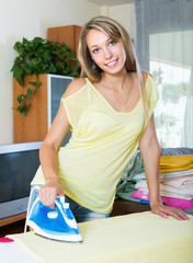 Blonde woman ironing at home