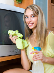 Smiling woman  wiping the dust on TV